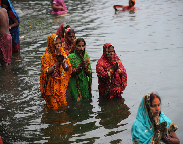 Indian Hindu devotees perform rituals during Chhat Puja while standing in the river in Kolkata.