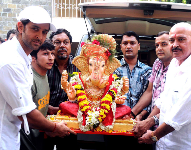 Indian Bollywood actors Hritik Roshan (L) and Rakesh Roshan (R) carry an elephant-headed Hindi God Lord Ganesh to immerse in water for blessings during a Hindu festival in Mumbai.