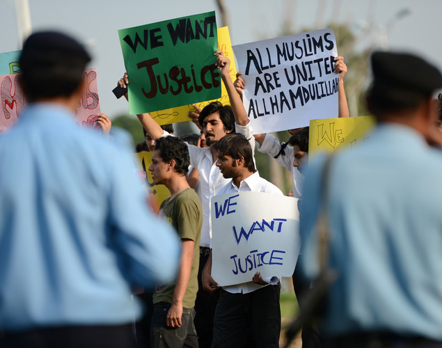Pakistani police watch students holding placards during a protest against the controversial film 'Innocence of Muslims' in Islamabad.