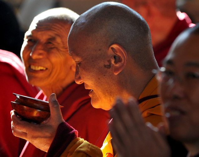 A Tibetan Buddhist monks sips tea while watching spiritual leader The Dalai Lama conduct a prayer meeting at The Namgyal Monastery in Dharamshala.