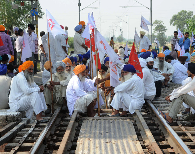 Indian farmers block traffic on a national highway during a protest against the state and central government at Rayya village some 35 kms from Amritsar.