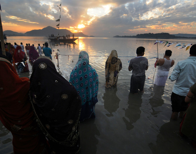 Indian Hindu devotees offer prayers to the sun during The Chhat Festival on the banks of the River Brahmaputra in Guwahati.