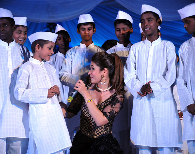 Indian entertainer Raageshwari Loomba (C) displays a creation by designer Neeta Lulla as she sings during a fashion show entitled Walk of  peace in Mumbai.