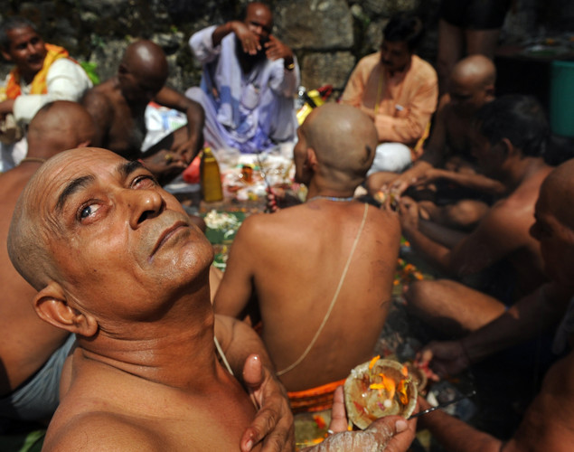 An Indian Hindu devotee looks up skyward as he and others perform 'Tarpan', a ritual to pay obesience to one's forefathers, on the last day for offering prayers to ancestors called 'Pitrupaksh' in Mumbai.