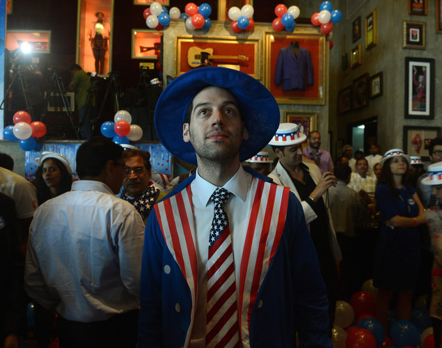 A US citizen watches the counting of votes on a large screen at an US Election Returns party in Mumbai.