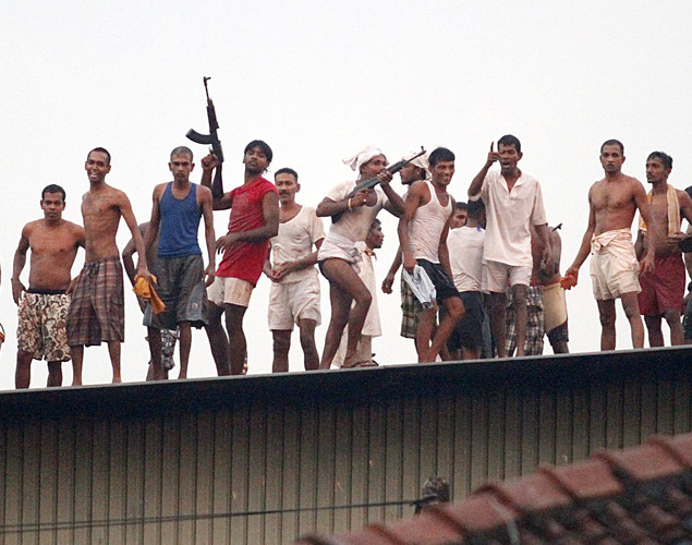 Sri Lankan prisoners climb onto a roof to get a view of a building set on fire by rioting inmates at Welikada prison in Colombo.