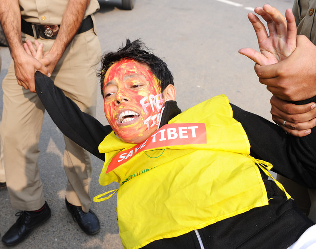 Indian police detain a Tibetan activist shouting slogans during a protest near the Chinese embassy in New Delhi.