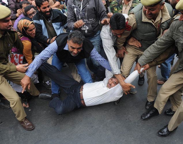 Indian police officials detain a Kashmiri government employee during a demonstration in Srinagar.