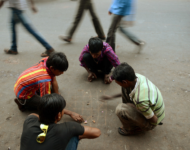 Indian youths play a game on a street in the walled city of Ahmedabad.