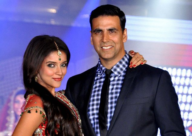 Akshay Kumar (R) and Asin walk the ramp wearing creations by designer Aki Narula during the promotion of their upcoming Hindi film 'Housfull 2'