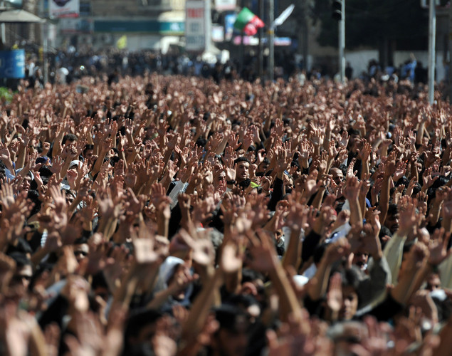 Pakistani Shiite Muslim mourners raise their hands during an Ashura procession in Karachi.