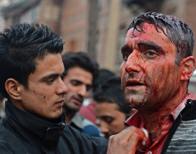A bloodied Kashmiri Shiite Muslim looks on after performing a ritual of self-flagellation with knives during a religious procession held on the fourth day of Ashura, which remembers the slaying of the Prophet Mohammed's grandson in southern Iraq in the seventh century, in Srinagar.