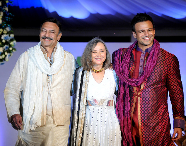 Indian Bollywood actors Suresh Oberoi (L) and Vivek Oberoi (R) flank US national Kia Scherr (C) as they display creations by designer Krishna Mehta during a fashion show entitled Walk of  peace in Mumbai.