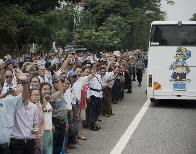 Supporters of US President Barack Obama and Myanmar pro-democracy leader Aung San Suu Kyi are seen outside her residence as they wave to a convoy carrying journalists who follows Obama and Suu Kyi in Yangon.