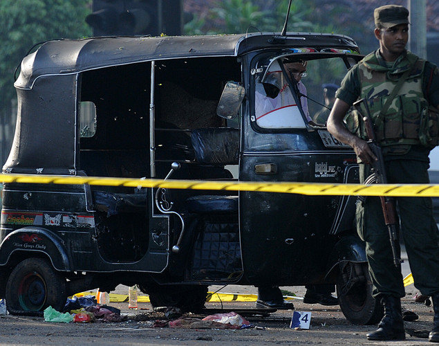 Sri Lankan soldiers stand guard near the three-wheel taxi allegedly used by inmates to escape from the Welika maximum prison in Colombo.