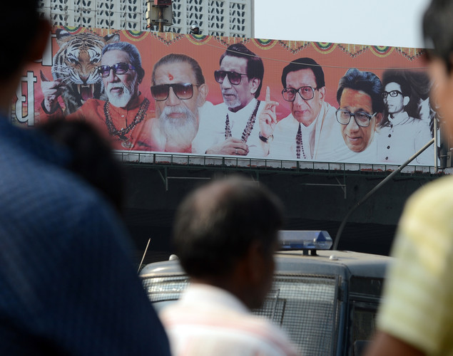Onlookers stand near a poster bearing portraits of ailing right-wing Hindu party Shiv Sena supremo Bal Thackeray, erected near his residence in Mumbai.