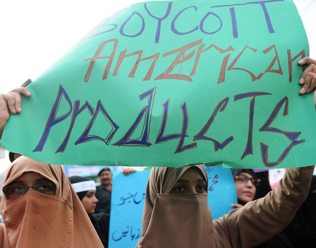 Veiled Pakistani protesters hold banners during a protest against an anti-Islam film at Karachi.