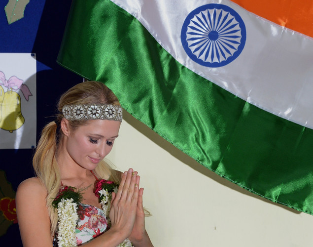 Paris Hilton folds her hands in a namaste - traditional Indian greeting as she stands alongside the Indian national flag during a visit to an orphanage in Mumbai.