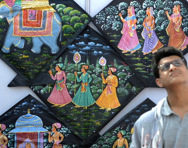An Indian youth watches kites fly during the Delhi International Kite Festival 2012 on the lawns of the India Gate monument in New Delhi.