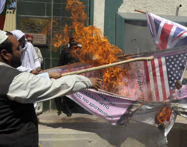 Pakistani Muslim demonstrators burn a banner with a US flag on it during a protest against an anti-Islam film in Quetta.