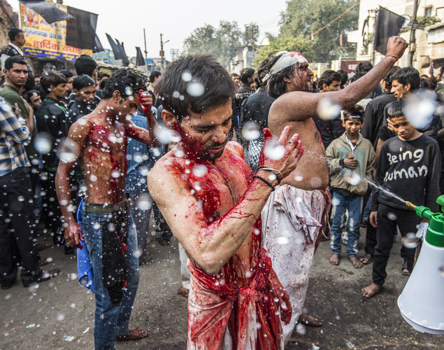 Water is sprayed onto Shiite Muslim men as they beat their chests, holding razor blades, as part of a self-flagellation ritual during a religious procession marking Ashura in New Delhi, India.