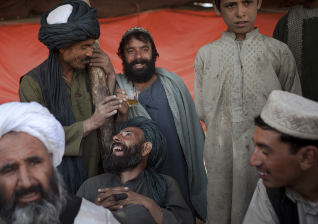 In this Oct. 23, 2012 photo, Afghan men gather at a crowded bus stop in the center of Lashkar Gah to catch a bus to Sangin, Afghanistan.