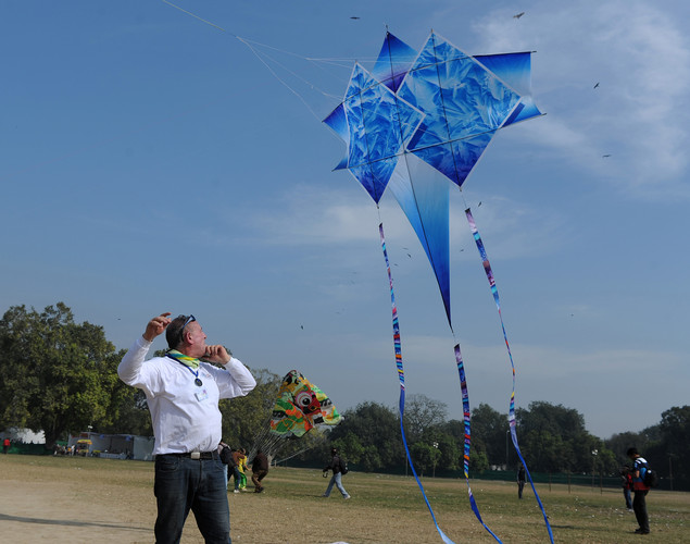 A visitor attempts to launch a kite during the Delhi International Kite Festival 2012 on the lawns of the India Gate monument in New Delhi.