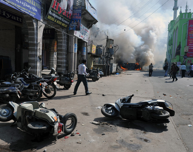 Toppled scooters and a burning vehicle are pictured outside a mosque following violence after Friday congregational prayers in the old city section of Hyderabad.