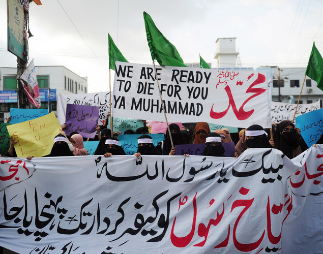 Veiled Pakistani protesters hold a banner during a protest against an anti-Islam film at Karachi.