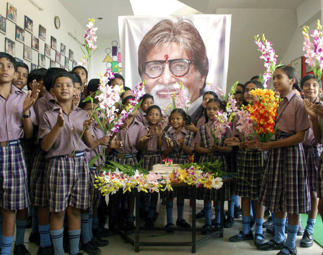 Indian schoolchildren stand in front of a portrait of Bollywood's biggest star Amitabh Bachchan, at an event a day ahead of his 70th birthday, in Mirzapur, India.