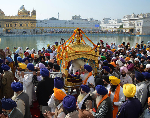 Indian Sikh devotees carry The Palki Sahib (Sikh holy book) during a procession from The Sri Akal Takhat at The Golden Temple in Amritsar on November 27, 2012 on the eve of the 543rd birth anniversary of Sri Guru Nanak Dev.