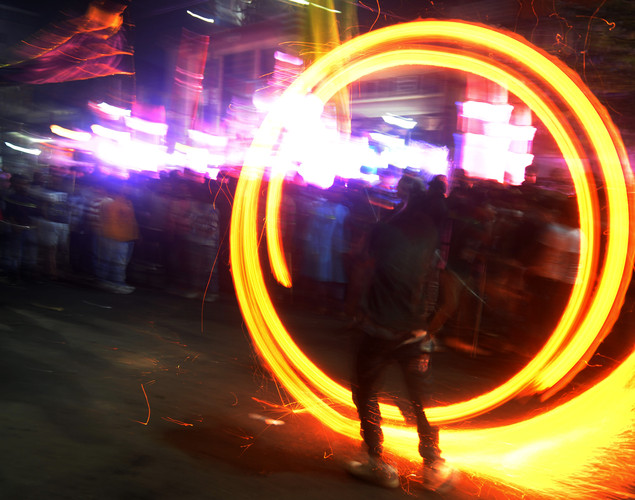An Indian Muslim spins a fire during a religious procession on the tenth day of the holy Islamic month of Moharram in Siliguri, West Benga.