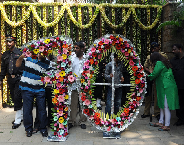 Indian security guards inspect a floral arrangement in the shape of the number seventy at the entrance of Bollywood actor Amitabh Bachchan residence on his 70th birthday in Mumbai.