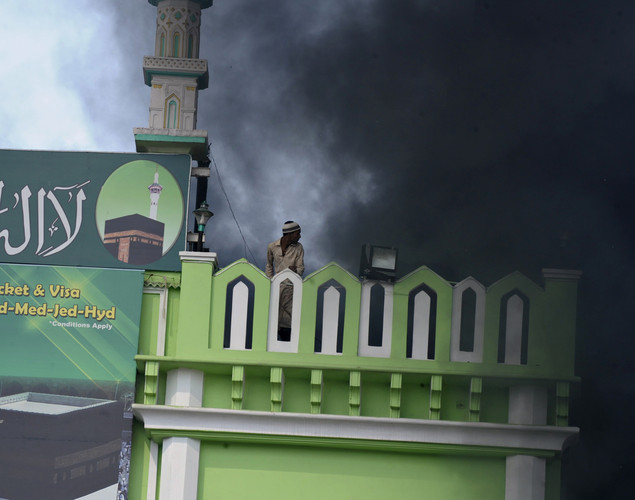 A Muslim youth looks on from the roof of a mosque amid rising smoke from burning vehicles during violence after Friday congregational prayers in the old city section of Hyderabad.