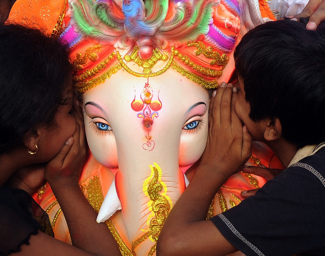 Indian Hindu devotees whisper their wishes into the ear of an idol of elephant-headed Hindu god Ganesha during a ritual before immersion at the iconic Juhu Chowpatty beach on the fifth day of the eleven-day long festival Ganesh Chaturthi, in Mumbai.