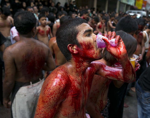 A man drinks juice while takes a break in a self-flagellation ritual as Shia muslims mark the Day of Ashura, striking themselves till they are bloody with razors and chains in Yangon, Myanmar.