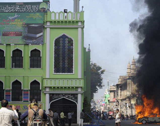 Bystanders watch as smoke rises from a burning car following violence after Friday congregational prayers in the old city section of Hyderabad.