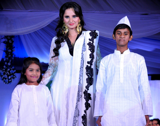 Indian tennis player Sania Mirza (C) walks with children displaying creations by designer Neeta Lulla during a fashion show entitled Walk of  peace in Mumbai.