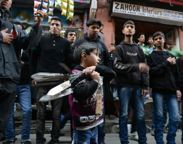 A child swings blades as other Kashmiri Shiite Muslims perform a ritual of self-flagellation with knives during a religious procession held on the fourth day of Ashura, which remembers the slaying of the Prophet Mohammed's grandson in southern Iraq in the seventh century, in Srinagar.