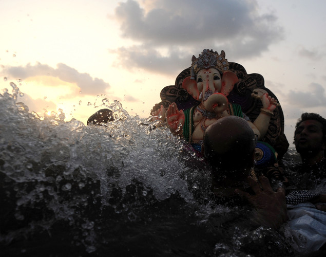 Indian Hindu devotees carrying an idol of elephant-headed Hindu god Ganesha brave a high wave during immersion at the iconic Juhu Chowpatty beach on the fifth day of the ten-day long festival Ganesh Chaturthi, in Mumbai.
