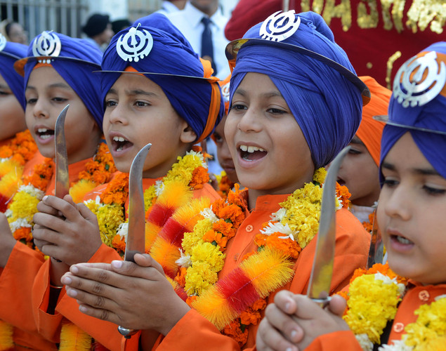 Indian Sikh boys dressed as Punj Pyara raise slogans during a procession at The Sikh Shrine Golden Temple in Amritsar on November 27, 2012 on the eve of the 543rd birth anniversary of Sri Guru Nanak Dev.