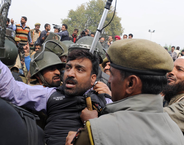 Indian police detain a Kashmiri government employee during a demonstration in Srinagar.