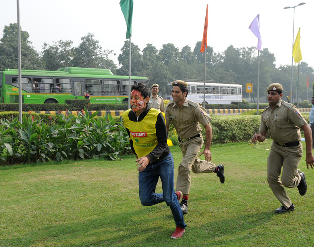 Indian police chase a Tibetan activist shouting slogans during a protest near the Chinese embassy in New Delhi.