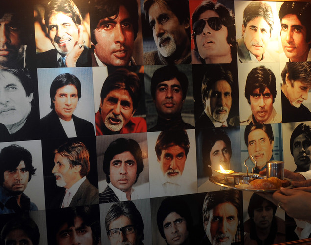 A fan of Indian Bollywood actor Amitabh Bachchan performs a prayer in front of a banner of photographs to celebrate his 70th birthday in Kolkata.