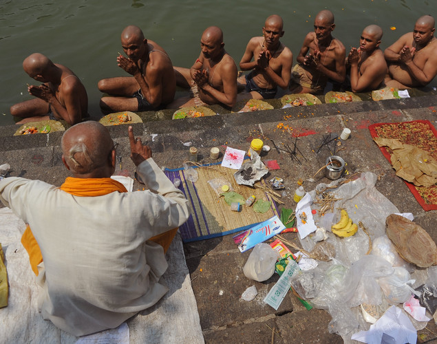A priest assists Indian Hindu devotees perform 'Tarpan', a ritual to pay obesience to one's forefathers, on the last day for offering prayers to ancestors called 'Pitrupaksh' in Mumbai.