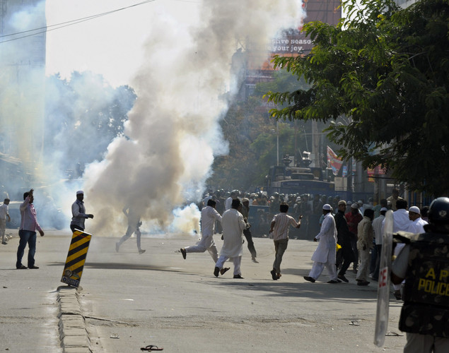 Muslim demonstrators disperse as Indian police fire teargas during violence after Friday congregational prayers in the old city section of Hyderabad.