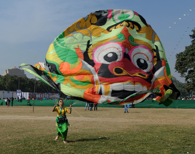 A visitor launches a kite during the Delhi International Kite Festival 2012 on the lawns of the India Gate monument in New Delhi.