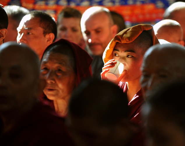 A Tibetan Buddhist monk drinks tea while watching spiritual leader The Dalai Lama conduct a prayer meeting at The Namgyal Monastery in Dharamshala.