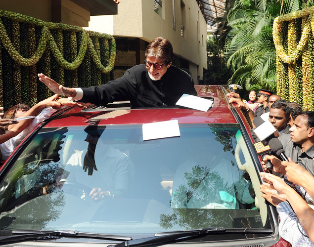 Bollywood star Amitabh Bachchan (C) reaches out to touch fans gathered outside his residence on his 70th birthday in Mumbai.