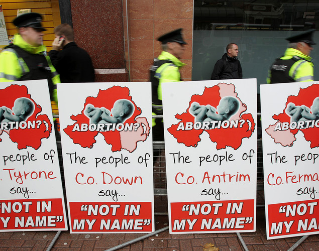 Police walk around abortion protestors hold up placards outside the Marie Stopes clinic, the first private clinic to offer abortions to women in Belfast, Northern Ireland on October 18, 2012.
